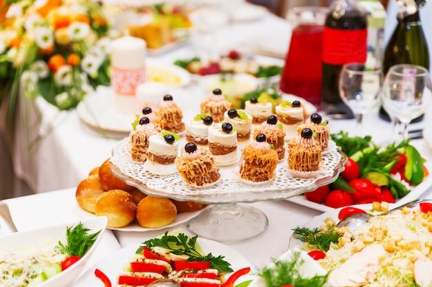 オレンジ色の結婚式の宴会用のテーブルセット。サラダ、前菜、ワイングラス。 Premium写真