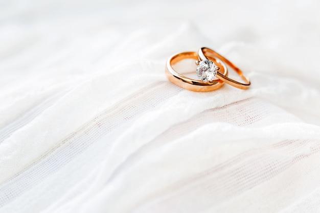 ダイヤモンドの黄金の結婚指輪は、白い布にうそをつきます。愛と結婚の象徴。 Premium写真