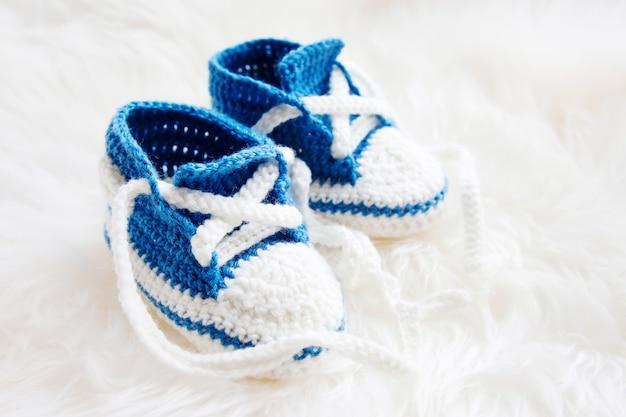 小さなベビーシューズ。生まれたばかりの少年や少女のための最初のスニーカー。かぎ針編みの手作りブーティ Premium写真