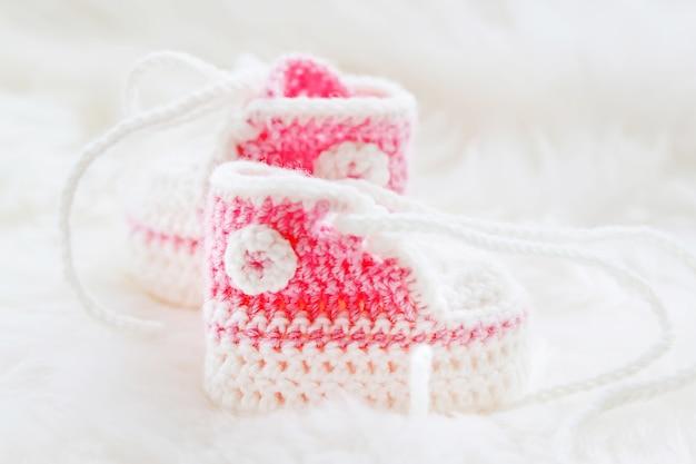 小さなベビーシューズ。生まれたばかりの女の子のための手編みの最初のスニーカー。かぎ針編みの手作りブーティ Premium写真