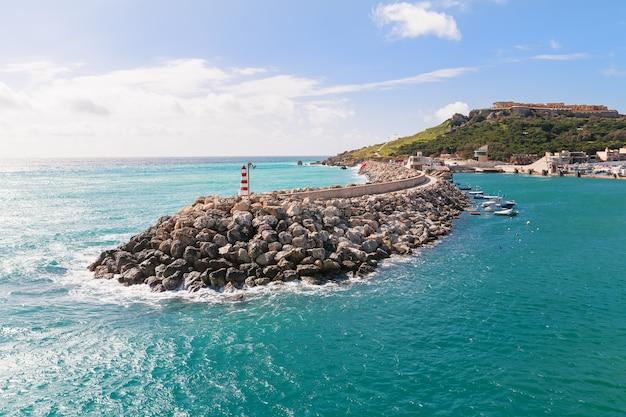 湾の入り口、防波堤上の灯台のある海辺。マルタのゴゾ。 Premium写真