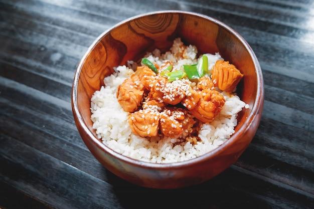 木製ボウルに野菜とサーモンを炒めたソースのご飯 Premium写真