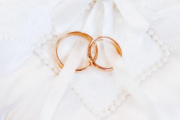 白い絹の背景に金色の結婚指輪。結婚式の詳細。愛と結婚の象徴。 Premium写真