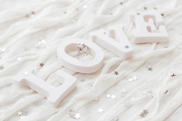 Слово любовь на белой ткани с обручальным кольцом с бриллиантом. хорошо для валентинки. Premium Фотографии