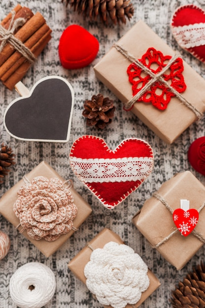 Сердечки на день святого валентина, подарки из крафт-бумаги с цветами крючком, сосновые шишки, красная шкатулка для подарков. Premium Фотографии