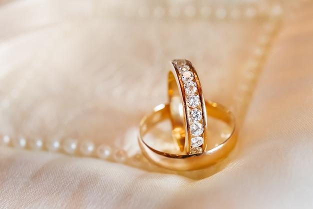 シルク生地にダイヤモンドをあしらった黄金の結婚指輪。ウェディングジュエリーの詳細。 Premium写真