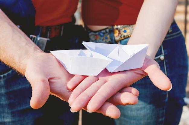 男と女の紙のペアを保持している手のひらに出荷します。カップルは愛と一体感のシンボル。 Premium写真