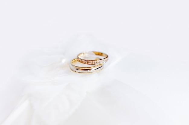 シルク生地にダイヤモンドをあしらった黄金の結婚指輪 Premium写真