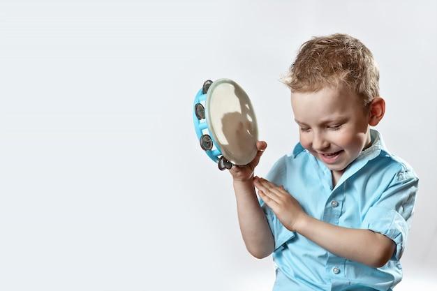 Веселый мальчик в синей рубашке держит бубен и улыбается на светлом фоне Premium Фотографии