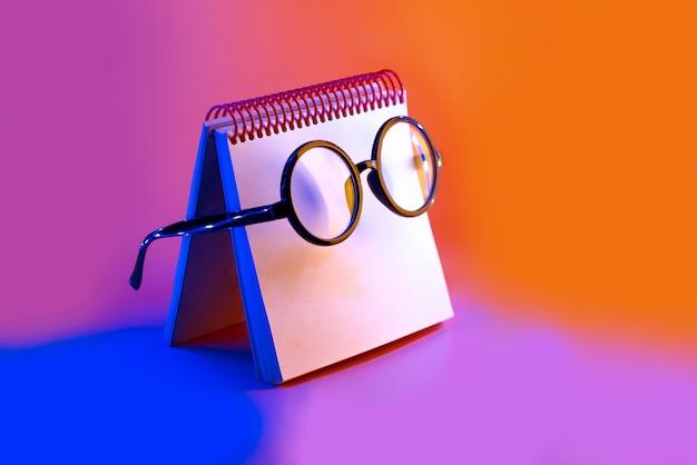 ピンクのネオンの光でメモ帳に横に黒い丸いメガネ Premium写真