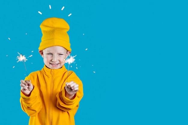 黄色の帽子とジャケットの小さな元気な子は青い背景に彼の手で燃える花火を保持します Premium写真