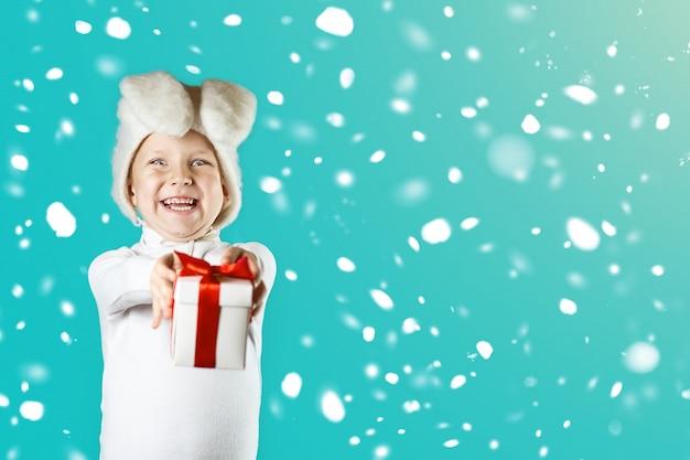 白いウサギの衣装を着た陽気な男の子は赤いリボンで贈り物をします。雪が降っている Premium写真