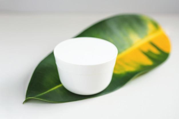 緑の葉の上に白いクリームが立っています。 Premium写真