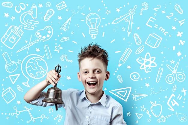 Мальчик в легкой рубашке улыбается и звонит в колокольчик. вокруг него различные школьные иконки на синем Premium Фотографии