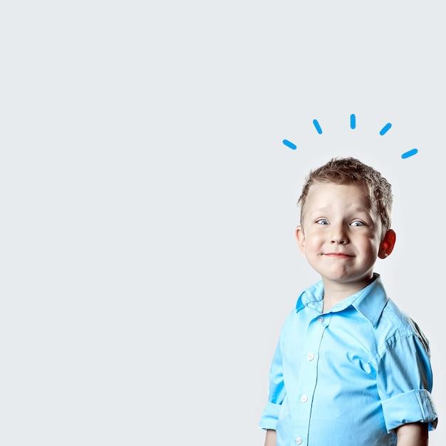 明るい背景に青いシャツを着て笑顔幸せな少年 Premium写真