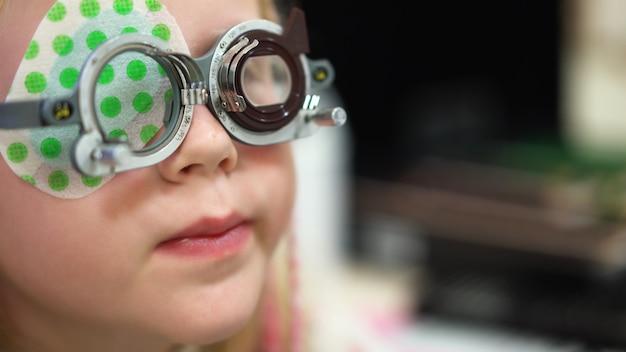 視力検査視覚障害のある白人の女の子。治療とリハビリテーション Premium写真