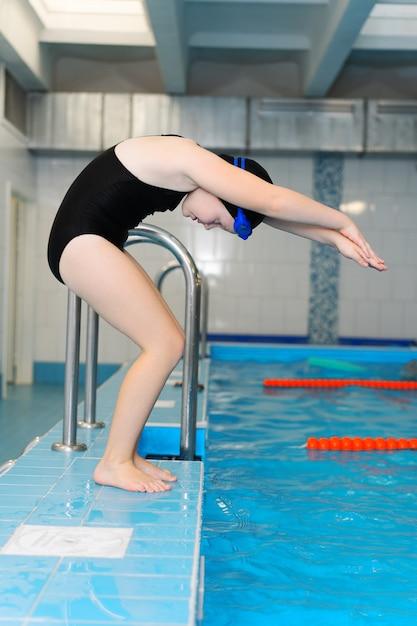 Уроки плавания для детей в бассейне - красивая белокурая девушка плавает в воде Premium Фотографии