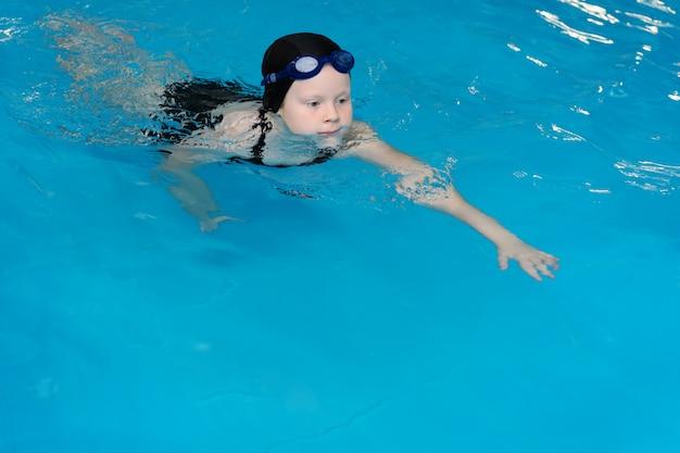 プールで子供のための水泳レッスン - 美しい色白の女の子は水で泳ぎます Premium写真