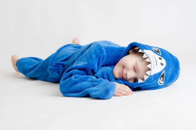 Веселый маленький мальчик позирует на белом в пижаме, синий костюм акулы Premium Фотографии