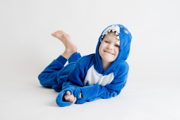 Веселый маленький мальчик позирует на белом фоне в пижаме, синий костюм акулы Premium Фотографии