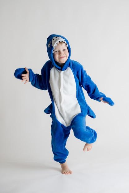 Веселый маленький мальчик позирует на белом фоне в пижаме кигуруми, синий костюм акулы Premium Фотографии