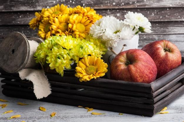 Хризантема в жестяной банке и яблоках Premium Фотографии