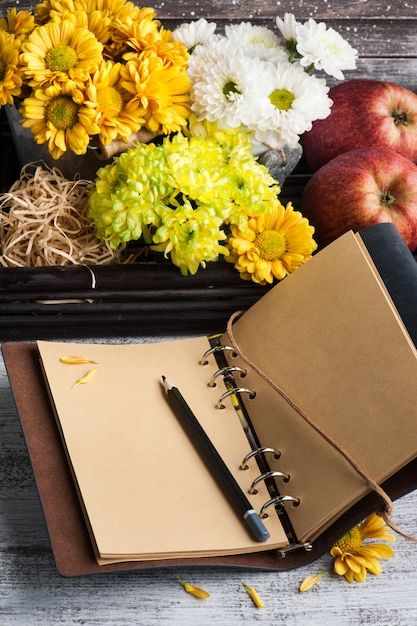 Пустой блокнот с зажженными огнями и хризантемой Premium Фотографии