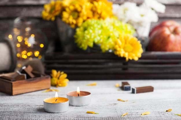 Зажгли свечи, хризантемы и зажгли огни Premium Фотографии
