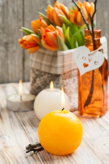 オレンジ色のチューリップ、キャンドルの花束 Premium写真