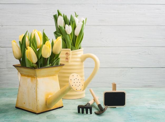 Весенние тюльпаны в желтой вазе и лейке Premium Фотографии