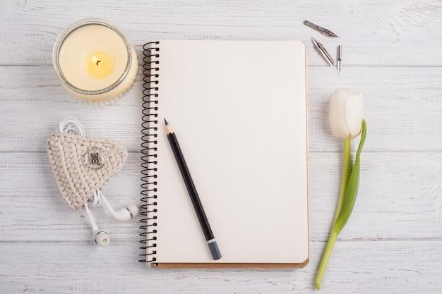 ノートブック、鉛筆、キャンドル、イヤーポッド、チューリップを開く Premium写真