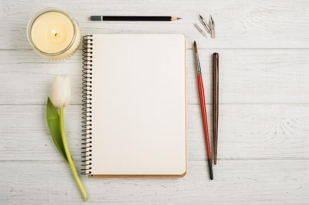 ノートブック、鉛筆、キャンドル、ブラシ、チューリップを開く Premium写真