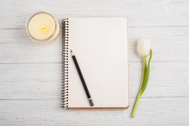 ノートブック、鉛筆、キャンドル、チューリップを開く Premium写真