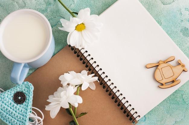 ノートブックを開く、イヤホン、ミルクのマグカップ Premium写真