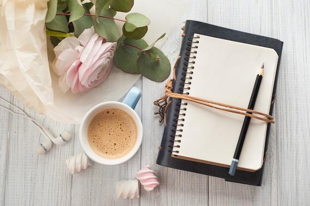 空白のノートブック、花束、コーヒーカップ、イヤホンを開く Premium写真