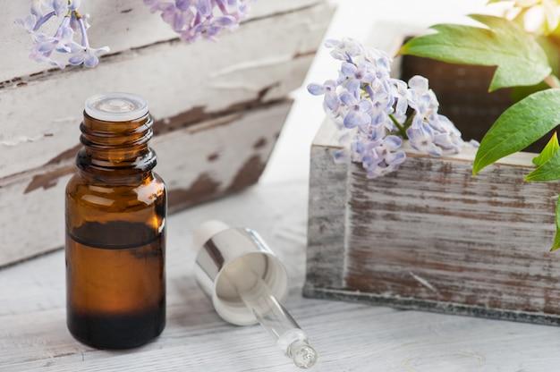 新鮮なライラックの花とエッセンシャルオイルのボトル Premium写真