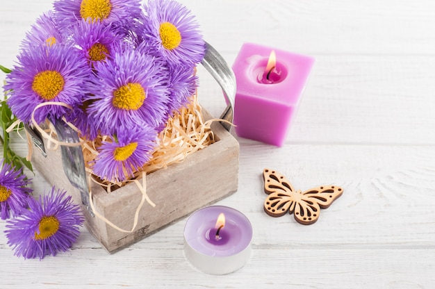 Фиолетовые ромашки и зажженные свечи на белом столе Premium Фотографии