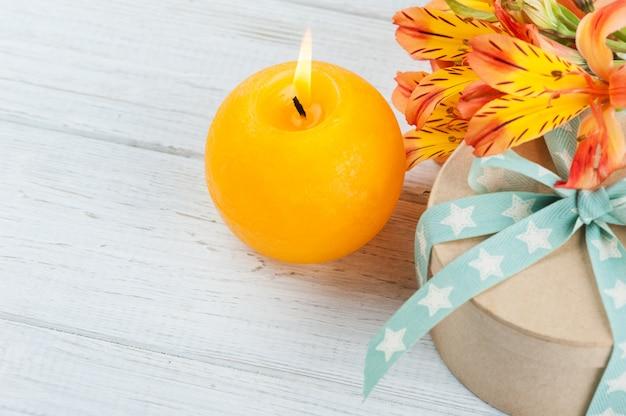 オレンジ色のユリの花とキャンドルの配置 Premium写真
