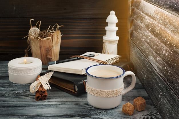 メモ帳、ろうそく、鉛筆、コーヒーを開く Premium写真