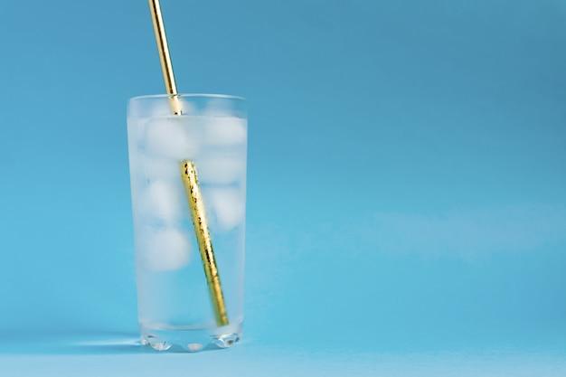 背の高い透明なガラスと太陽のまぶしさで氷と金の紙のストローで純水のクローズアップ。コピースペース Premium写真
