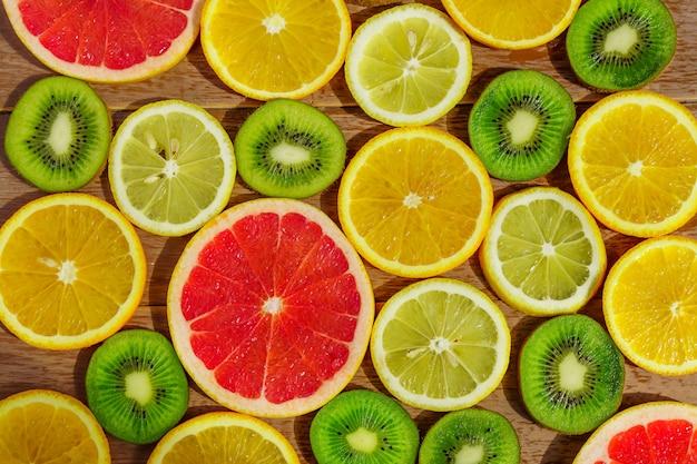オレンジ、レモン、キウイ、グレープフルーツパターンのスライスとフレームが分離されました。 Premium写真