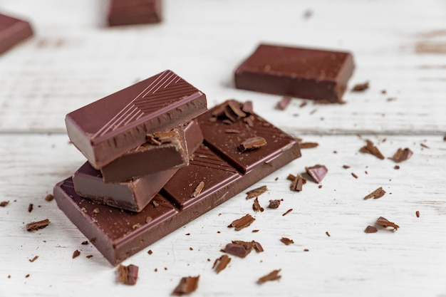 木製のテーブルの上のチョコレートバー。ダークチョコレートの破片 Premium写真