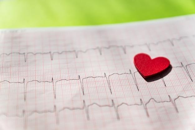 Закройте вверх электрокардиограммы в бумажной форме с красным деревянным сердцем. экг или экг на черном фоне. концепция медицины и здравоохранения. Premium Фотографии