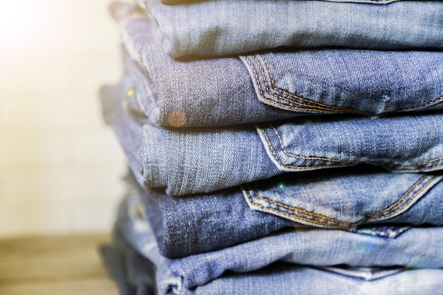 Стог голубых джинсов на деревянной полке в солнечном свете. концепция красоты и модной одежды Premium Фотографии