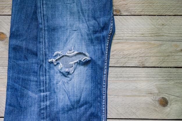 Взгляд сверху голубых увяданных джинсов с отверстием на деревянной поверхности. красота, мода и концепция покупок. Premium Фотографии