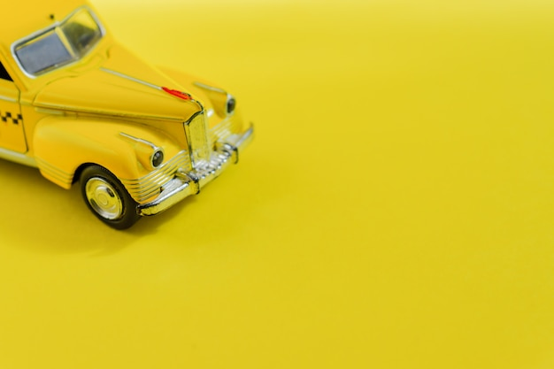 Старый ретро желтый игрушечный автомобиль такси на желтом Premium Фотографии