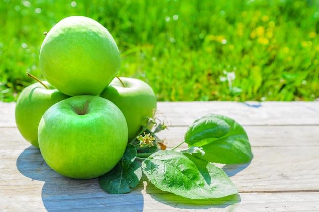 Свежесрезанные зеленые яблоки на деревянный стол на зеленой траве Premium Фотографии