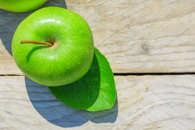 木製のテーブルに新鮮なトリミングされた緑のリンゴ Premium写真