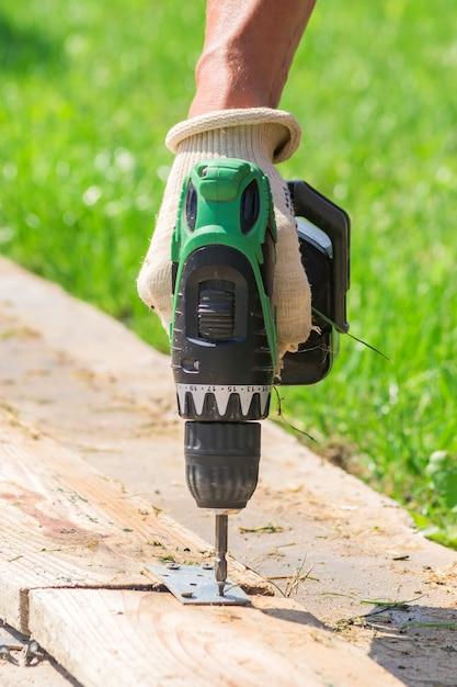 男性の電動ドライバーは、繊維手袋を屋外で手します。裏庭の手のひらツールで作業する人。 Premium写真