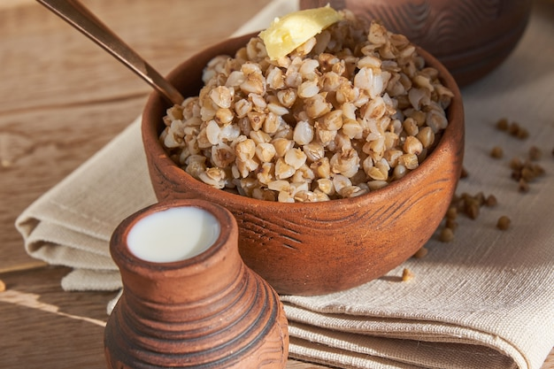 Закройте гречневую кашу с маслом в миску на белом деревянном Premium Фотографии